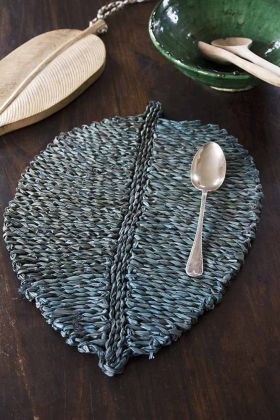 Lifestyle image of the Leaf Shaped Seagrass Placemat In Petrol Blue