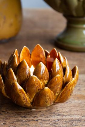 Lifestyle image of the Handmade Amber Ceramic Artichoke Candle Holder