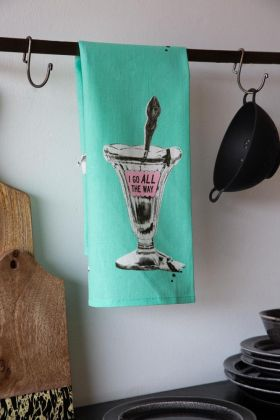 Lifestyle image of the I Go All The Way Retro Tea Towel on a black rail