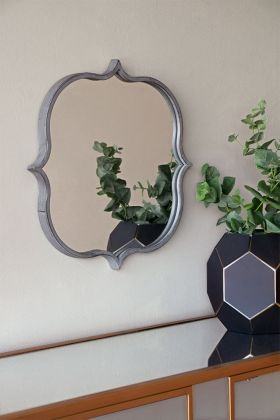 Lifestyle image of Indoor Or Outdoor Marrakesh Mirror with burnished silver metal ornate frame hanging on a wall