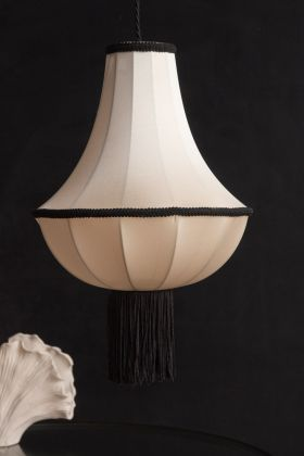 Lifestyle image of the Cream & Black Lantern Ceiling Light Shade With Tassels on a dark background