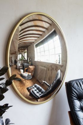 Close-up lifestyle image of the Large Round Antique Brass Foxed Mirror