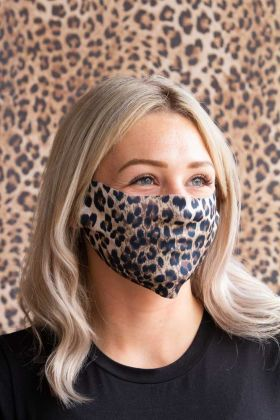 Lifestyle Image of the Leopard Print Face Mask Worn By A Woman Standing Against A Leopard Print Background