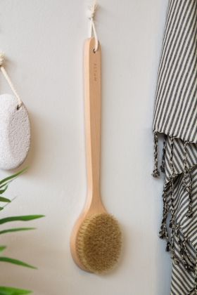 Lifestyle image of the Long Handled Beech Wood Bath Brush hanging on the wall
