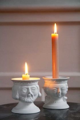 Lifestyle image of the Set Of 2 White Ceramic Fairytale Candlestick Holders with lit candles