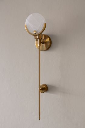 Angled image of the Marble Disc & Brass Wall Light on the wall