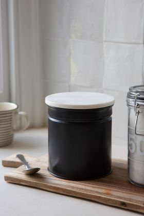 Lifestyle Image of the Matt Black Steel Canister With White Marble Lid on a breadboard