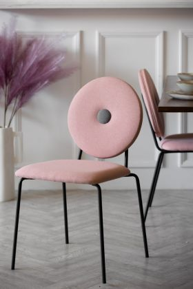 Lifestyle image of Modern Round Back Dining Chair In Blush Pink with white panelled wall in the background and wooden top dining table and pink faux flowers