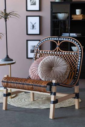 Lifestyle image of the Black & Natural Beautiful Rattan Lounge Chair with two Vintage Style Velvet Rouched Round Cushions on it