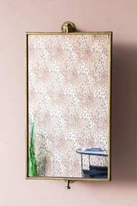 Lifestyle image of the Rectangular Swivel Wall Mirror hanging on the wall