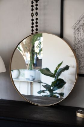 Front angled lifestyle image of the Medium Round Gold Framed Wall Mirror