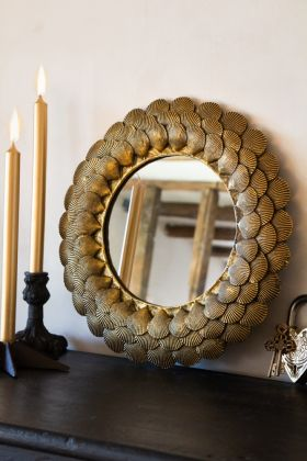 Lifestyle image of the Round Mirror With Antique Gold Shell Layers sat on a dresser