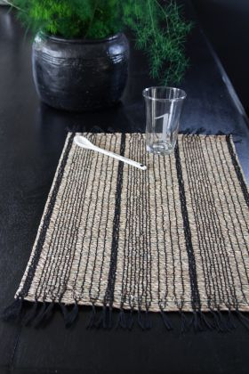 Lifestyle image of the Seagrass Black & Natural Placemat with angled spoon & glass