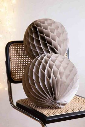 Lifestyle image of the Set Of 2 Honeycomb Ball Decorations In Stone Grey on a chair