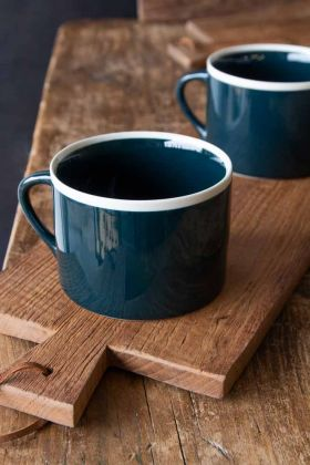 Lifestyle image of the Set Of 2 Large Teal Coffee Mugs With White Rim