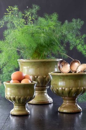 Lifestyle image of the Set Of 3 Roman-Style Distressed Green Urn Flower Pots