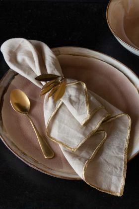 Lifestyle image of the Set Of 4 Champagne Cotton Napkins With Gold Trim