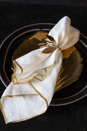 Lifestyle image of the Set Of 4 White Cotton Napkins With Gold Trim