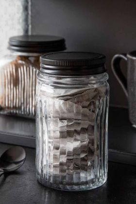 Lifestyle image of the Tall Glass Storage Jar With Black Metal Lid