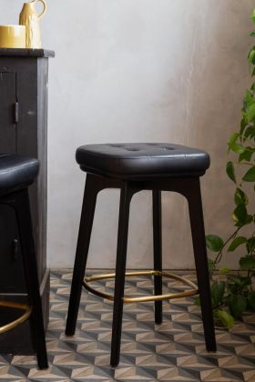 Lifestyle image of the Timeless Mid-Century Style Bar Stool In Black