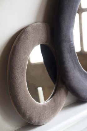 Lifestyle image of the Round Velvet Frame Mirror In Dusky Pink next to the Charcoal Grey version