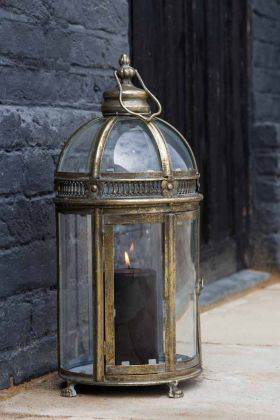 Lifestyle image of the Vintage Style Glass & Distressed Metal Lantern with a lit pillar candle inside