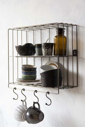 Lifestyle image of the Antique Brass Coloured Wire Wall Rack & Hooks filled with kitchen accessories and mugs hanging on hooks on white wall background