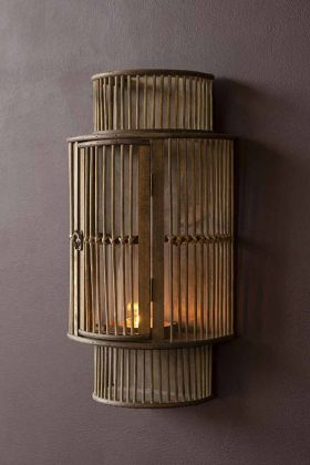Lifestyle image of the Bamboo Curved Wall Lantern with a candle lit inside it on briar-wood painted wall background