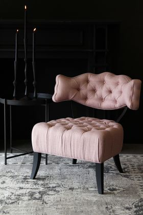 lifestyle image of cloud herringbone tweed chair - fille pink with black side table and large black candles on grey rug