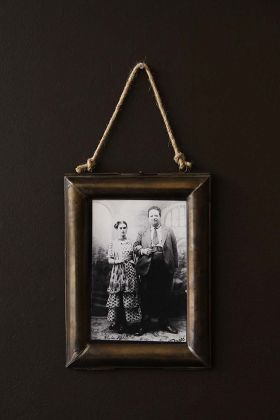 lifestyle image of Hanging Brass Picture Frame - Large wit black and white photograph inside on dark brown wall background