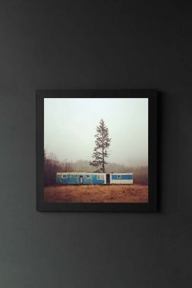 lifestyle image of unframed mini fine art print of forks, washington blue bungalow with tree and brown grass in black frame on dark wall background
