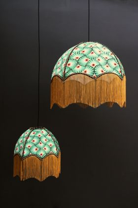lifestyle image of two Anna Hayman Designs DecoFabulous Green & Orange Palm Print Pendant Shade with dark wall background