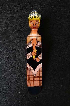 Lifestyle image of the Queen B Door Stop on dark floor background