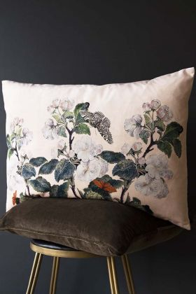 Lifestyle image of the apple blossom floral butterfly velvet cushion in nude pink on a stool with dark wall background