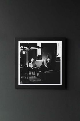 lifestyle image of Unframed Three Chefs Art Print By Jamie Waters black and white photograph of chefs in restaurant in black frame on dark wall background