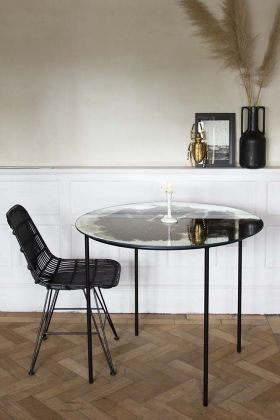 Lifestyle image of the Vintaged Glass Mirror & Iron Round Dining Table on wooden parquet floor and white wall background with black rattan chair and accessories