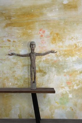 Lifestyle image of Feathr Oh La La Wallpaper by Kiki Slaughter - Gold with brown wooden bench and distressed stone figure holding arms out
