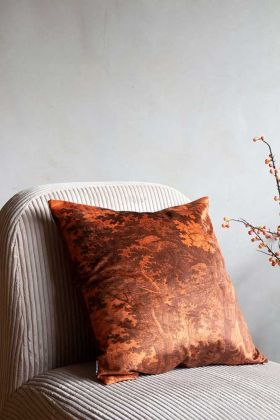 Image of the Burnt Orange In The Woods Velvet Cushion sat on a chair