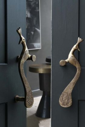 lifestyle image of Set Of 2 Elegant Brass Peacock Door Handles on two grey doors one slightly ajar