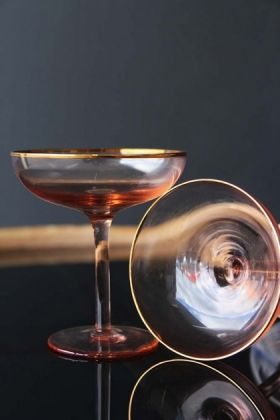 lifestyle image of Set Of 2 Rose Pink & Gold Champagne Coupe on black table with dark wall background