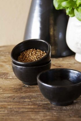 Lifestyle image of the Set Of 3 Black Brown Terracotta Dipping Bowls with seeds inside on wooden shelf with black terracotta vase in background