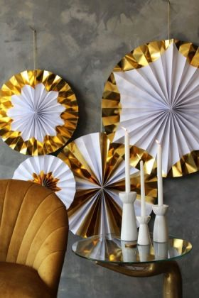 lifestyle image of set of 4 foil giant pinwheel decorations - gold with the lovers velvet chair - golden glow and gold and glass side table with white candlesticks on