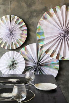 lifestyle image of Set Of 4 Hanging Holographic Silver Foil Pinwheel Decorations behind set black table and on distressed grey wall background