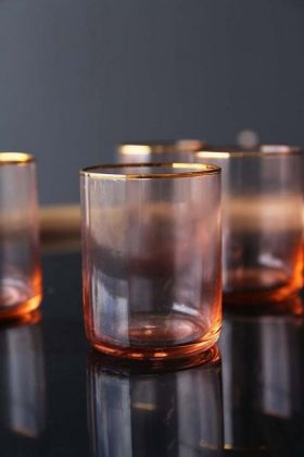 lifestyle image of Set Of 4 Rose Pink & Gold Water Glasses on black table with grey wall background