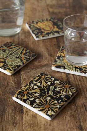 Lifestyle image of the Set Of 4 Vintage Style Floral Ceramic Coasters on a wooden surface with water glass