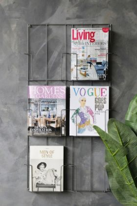 lifestyle image of six-tier magazine wall rack with four magazines inside and plant with grey wall background