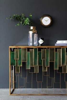 lifestyle image of Skyline Console Table with gold vase with plant and other ornaments and clock on grey wall background