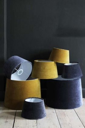 lifestyle image of Smokey Blue Sumptuous Velvet Lamp Shade - Small and yellow toned velvet shades in pile on wooden floor and dark wall background