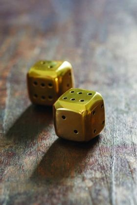 lifestyle image of Solid Brass Bevelled Dice on distressed leather background