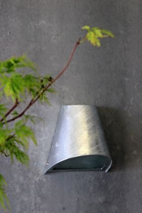 lifestyle image of st ives hot dipped funnel wall light on grey wall and plant in foreground
